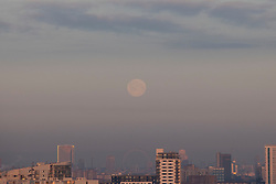 © Licensed to London News Pictures. 27/02/2021. London, UK. February's full moon, commonly known as the Snow Moon, sets behind the London skyline. The Snow Moon is also known as the Hunger Moon or the Storm Moon.  Photo credit: George Cracknell Wright/LNP