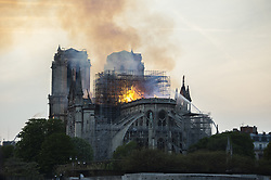 Smoke and flames rise during a fire at the landmark Notre-Dame Cathedral in central Paris on April 15, 2019, potentially involving renovation works being carried out at the site, the fire service said. Photo by Eliot Blondet /ABACAPRESS.COM