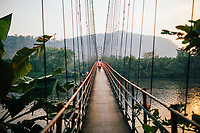 Neriamangalam, India -- February 17, 2018: A man walks across a suspension bridge on the Periyar River in Kerala.