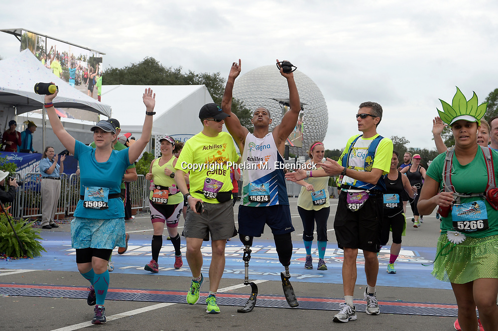 Msgt. Cedric King, center, is helped by guides Michael LoPresti, left, and David Cordani, CEO of Cigna Corp., after crossing the finish line during the Walt Disney World Marathon in Lake Buena Vista, Fla., Sunday, Jan. 10, 2016. (Photo by Phelan M. Ebenhack)