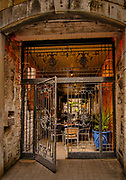 About the Subject: A passageway, originally built to give access for horse-drawn carriages, now a café with an elaborate entrance gate.<br /> <br /> About the Capture: Taken in the morning, in early Spring, this semi-alfresco café reaches through the passageway, lined with exposed brick and stone, to an inner courtyard. The gate is welcomingly ajar. The rich textures and earthy colours give a sense of warmth despite being in the open air while the heavy stone construction and wrought iron gates impart a feeling of strength and substance. The presentation in this capture accentuates the colours, contrasts, strength and inviting warmth of the scene.