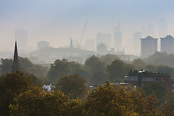 Primrose Hill, London, October 30th. The sun begins to break through as mist shrouds London's skyline, viewed from  Primrose Hill. Pictured: The city's skyline emerges from the morning mist.