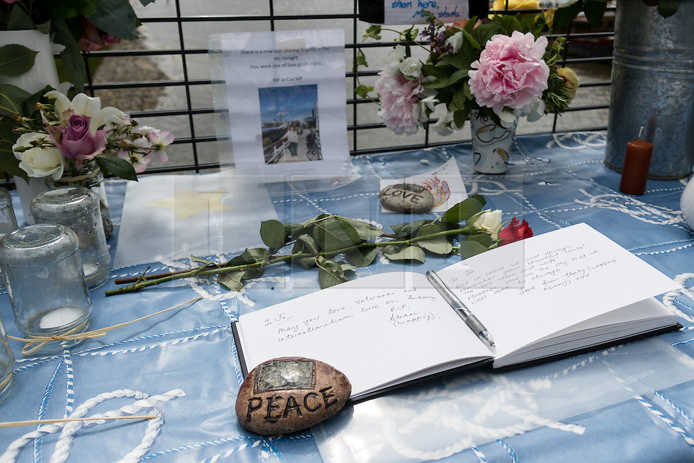 © Licensed to London News Pictures. 18/06/2016. LONDON, UK.  Floral tributes and stones of love and peace, with a condolence book on a tribute table outside Hermitage Moorings on the River Thames in Wapping, where the MP lived on a houseboat. The Labour MP for Batley and Spen was about to hold her weekly constituency surgery in Birstall Library on16 June 2016 when she was shot and stabbed in the street and later died. Friends and neighbours from the local community continue to visit Hermitage Moorings this morning to pay tribute to Jo Cox. Photo credit: Vickie Flores/LNP