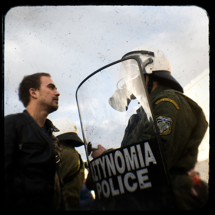 A man talking to a riot policeman in front of the Greek parliament. <br /> <br /> Following the murder of a 15 year old boy, Alexandros Grigoropoulos, by a policeman on 6 December 2008 widespread riots, protests and unrest followed lasting for several weeks and spreading beyond the capital and even overseas<br /> <br /> When I walked in the streets of my town the day after the riots I instantly forgot the image I had about Athens, that of a bustling, peaceful, energetic metropolis and in my mind came the old photographs from WWII, the civil war and the students uprising against the dictatorship. <br /> <br /> Thus I decided not to turn my digital camera straight to the destroyed buildings but to photograph through an old camera that worked as a filter, a barrier between me and the city.