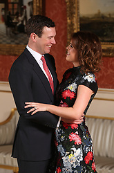 Princess Eugenie and Jack Brooksbank in the Picture Gallery at Buckingham Palace in London after they announced their engagement. Princess Eugenie wears a dress by Erdem, shoes by Jimmy Choo and a ring containing a padparadscha sapphire surrounded by diamonds.