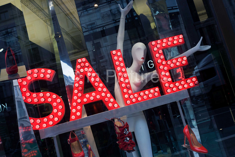 A Sale sign glows red with a mannequin in London's Regent Street shoe shop window. At a slight angle, the word Sale is seen in capital letters and the reflections of the city street outside merges with the red shoes displayed on sale. The female form of the mannequin is posed as a dancer, with arms outstretched and theatrical lipstick that matches the red lettering.