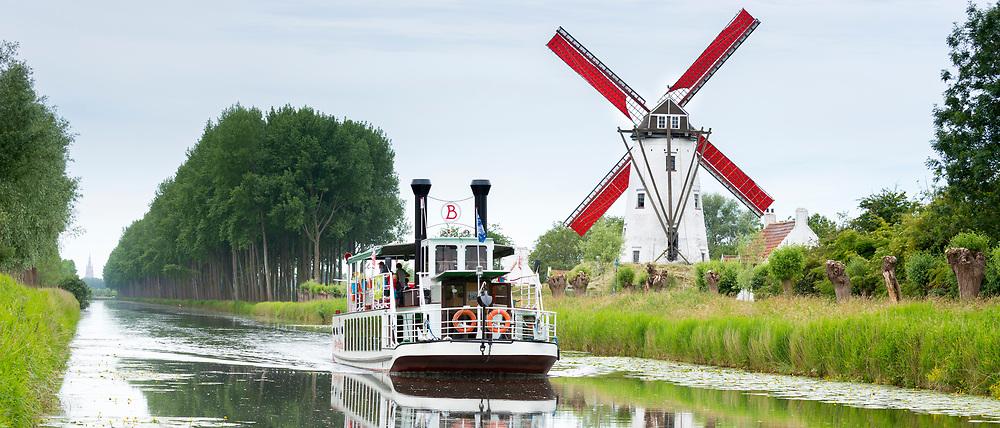 Tourist paddle steamer passes Schellemolen windmill on Damse Vaart Canal at Damme, West Flanders, Belgium