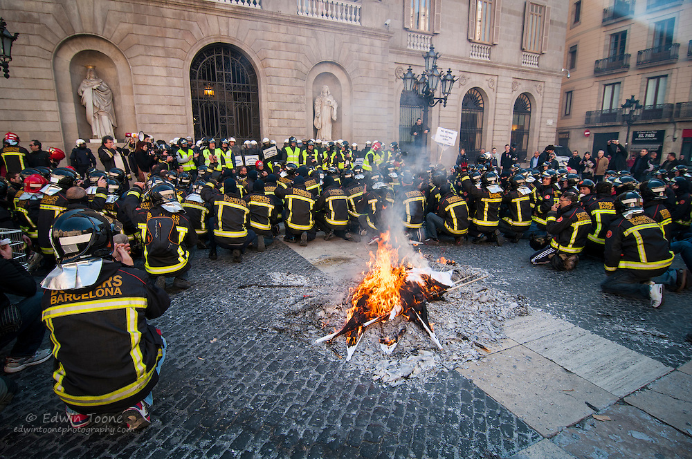Fire fighters kneel around a fire in Placa Sant Jaume in protest to budget cuts.