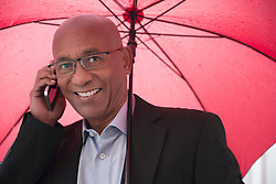 Man African holding umbrella mobile phone Positive