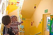 Toddler brother and mom age 1 and 28 visiting son's Rainbow Preschool Teczowe Przedszkole Balucki District Lodz Central Poland