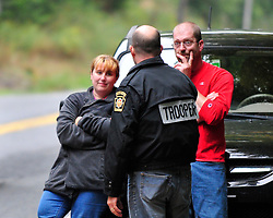 Displaced residents Jennifer and Jason Neff speak with a Pennsylvania State Trooper about returning to their home. The Neff's were evacuated from their home at 6:50pm Friday evening. Police surround a neighborhood in the Pocono Mountains in search of ambush suspect Eric Matthew Frein who is accused of shooting two Pennsylvania State Troopers Saturday Sept. 20th, 2014 in Canadensis, Pennsylvania (AP Photo/Chris Post)