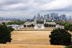 © Licensed to London News Pictures. 30/07/2018<br /> GREENWICH, UK.<br /> View across London Canary Wharf and Queen's House.<br /> A cloudy grey day in London, Greenwich Park, Greenwich.<br /> Photo credit: Grant Falvey/LNP
