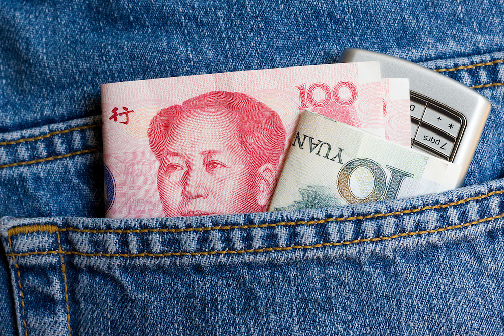 Chinese currency, one hundred and ten Yuan bills, and mobile phone in jeans pocket
