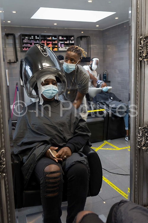 As the UK eases further from Coronavirus pandemic restrictions - a relaxation of rules such as one metre plus distance rule and the re-opening of pubs, bars, restaurants and hairdressers - staff and customers at the Carl Campbell hairdressers get used to social distancing and the wearing of PPE personal protection equipment face coverings in the salon, on Coldharbour Lane in Brixton, on 4th July 2020, in London, England. Under current in hair salons rules, to prevent the spread of airbourne droplets, conversation is meant to be kept to a minimum but the wearing by customers of face coverings is not actually mandatory.