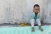 Young boy with flowers, hands on his face in deep thought at Shwemawdaw Pagoda