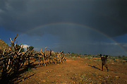 A double rainbow arches over a Hamar village and a Hamar girl who carries and infant on her hip, in South Omo, Ethiopia. The 40,000-strong, cattle-herding Hamar are among the largest of the 20 or so ethnic groups which inhabit the culturally diverse South Omo region in south-west Ethiopia.