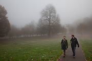 Thick fog over London making a peaceful yet eerie landscape atmosphere as people come out to go walking in Greenwich Park as the trees and grass disappear into the distance. Greenwich is a very popular destination for local people, Londoners and tourists to come to enjoy some time outdoors.