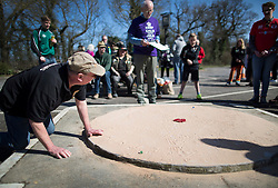 © Licensed to London News Pictures. 25/03/2016. Crawley, UK. A player takes a shot in the World Marbles Championships in the car park of the Greyhound pub in Tinsley Green near Crawley. The competition has taken place every year since 1932 with teams from the USA, Algeria, Australia and Europe taking part. Photo credit: Peter Macdiarmid/LNP