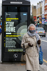 © Licensed to London News Pictures. 26/12/2020. London, UK. An elderly woman wearing a face covering in north London walks past the government's 'Coronavirus Tier 4 - Stay Home' publicity campaign poster as many parts of the UK entered the highest level of COVID-19 restrictions on Boxing Day after mutated COVID-19 strains continue to spread around the country. Prime Minister, Boris Johnson refused to rule out a third national lockdown in the New Year. Photo credit: Dinendra Haria/LNP