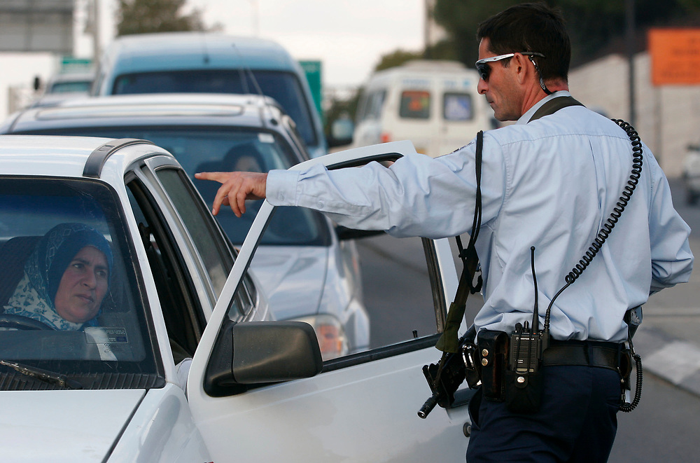 An Israeli police officer signals for an east Jerusalem Palestinian woman to stop her car for a security inspection, in Jerusalem, on November 25, 2007.