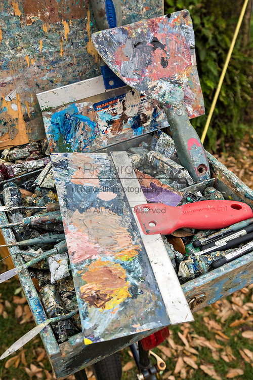 Paints and brushes belonging to artist David Anthony Babb known as DAB as he works on a painting using his dabism technique in the Cistern yard at the College of Charleston in Charleston, South Carolina.