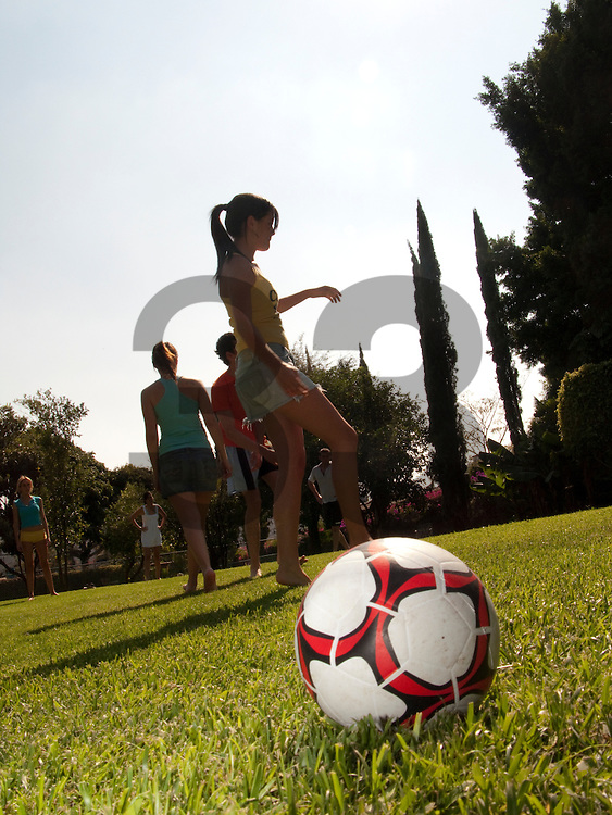A red and white soccer ball on a grass field with teenage girls in the background. Vertical shot.