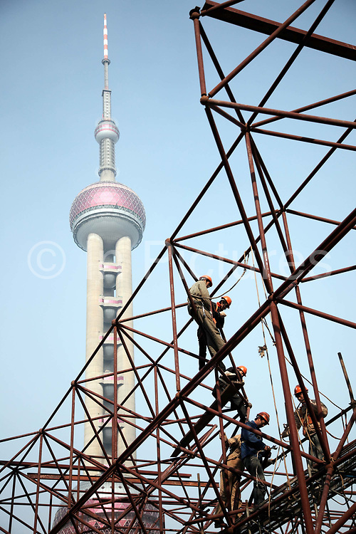 Construction workers operate on a scaffolding in front of the Pearl Oriental Tower in Shanghai, China on 18 December, 2009. Shanghai is on its way of becoming one of the world's most important financial centers.