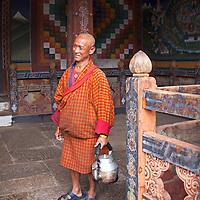 Asia, Bhutan, Trongsa. Monk with kettle at Trongsa Dzong.