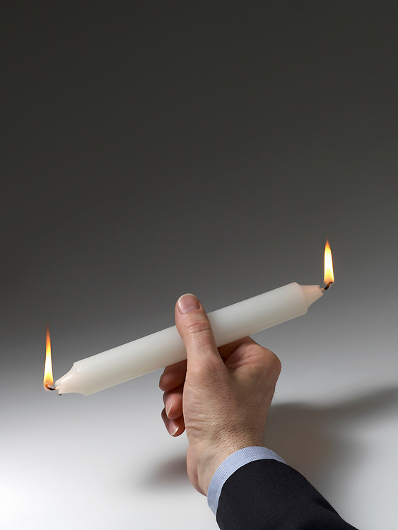 Man holding a candle that is burning at both ends