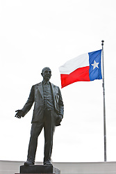 Texas flag and sculpture of George Bannerman Dealey in Dealey Plaza, Dallas, Texas, USA.