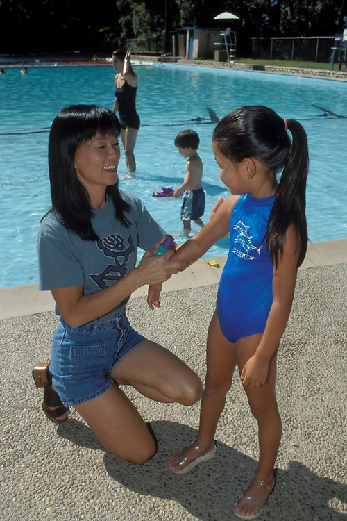 Asian-American mother applying sunscreen to  5 year old daughter while at a public pool.  Model Release.<br /> ©Bob Daemmrich