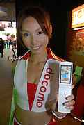 A member of staff for the Docomo (mobile phone carrier) stall. She is holding a mobile phone running a classic console game adapted for mobile phones.