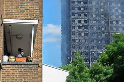 © Licensed to London News Pictures. 14/06/2017. London, UK.   A resident in an adjacent building wears a protective face mask.  The Grenfell Tower near Latimer Road in west London smoulders after it was engulfed in a huge fire the previous night, resulting in at least twelve fatalities with many more in critical condition. Photo credit : Stephen Chung/LNP