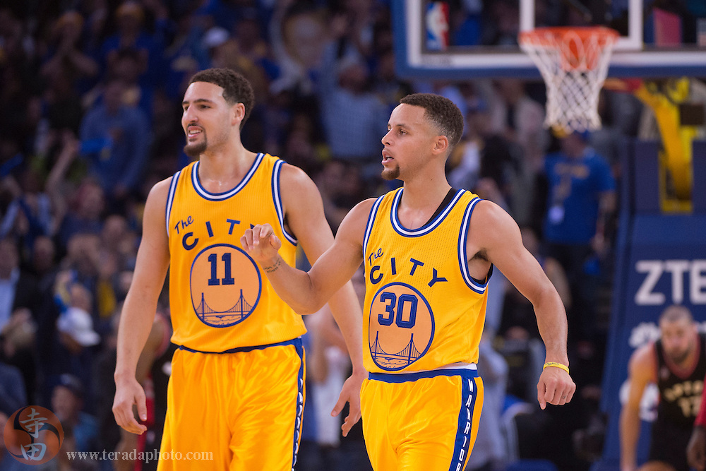 November 17, 2015; Oakland, CA, USA; Golden State Warriors guard Klay Thompson (11) and guard Stephen Curry (30) celebrate during the second quarter against the Toronto Raptors at Oracle Arena. The Warriors defeated the Raptors 115-110.