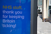 Homeless man passed out on the street near an HM Government, and NHS advertising boards thanking NHS staff in Birmingham city centre is virtually deserted due to the Coronavirus outbreak on 24th April 2020 in Birmingham, England, United Kingdom. Coronavirus or Covid-19 is a new respiratory illness that has not previously been seen in humans. While much or Europe has been placed into lockdown, the UK government has extended stringent rules as part of their long term strategy, and in particular social distancing, which has left usually bustling areas like a ghost town.