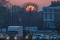 © Licensed to London News Pictures. 18/04/2021. London, UK. The sun rises behind trees on Blackheath Common in South East London. Temperatures are expected to rise with highs of 17 degrees forecasted for parts of London and South East England today . Photo credit: George Cracknell Wright/LNP