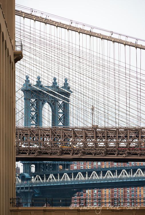 Manhattan Bridge, as seen through the cables of the Brooklyn Bridge, Brooklyn, New York.