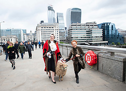 Simone Lakmaker, who set up the charity 'The Speaking Out Forum' in 2018 which is a platform for young people with physical and/or mental disabilities to speak in public is pictured on London Bridge, London, Great Britain <br /> 27th April 2019<br /> <br /> Simone Lakmaker<br /> Mark the Sheep <br /> Hon Elizabbeth Green<br /> (Lord Mayor's Sheriff)<br /> <br /> <br /> Simone Lakmaker, turning 80, who has for many years, been a Freeman of the City of London and as a freeman, she has the right to drive/walk sheep over London Bridge!  That's what she did with a sheep on  a lead from Spittalfields City Farm. <br /> <br /> She is. joined by the Lord Mayor's Sheriff the Hon Elizabbeth Green, who is a farmer herself and supports the woolmens' sheep walk over London Bridge, and a footman in full regalia.<br /> <br /> Her 24-year-old grandson, Toby Marlow, is one of the wriiters of smash-hit West End musical SIX (nominated for 5 Olivier Awards) about the six wives of Henry VIII.<br />  <br /> Photograph by Elliott Franks