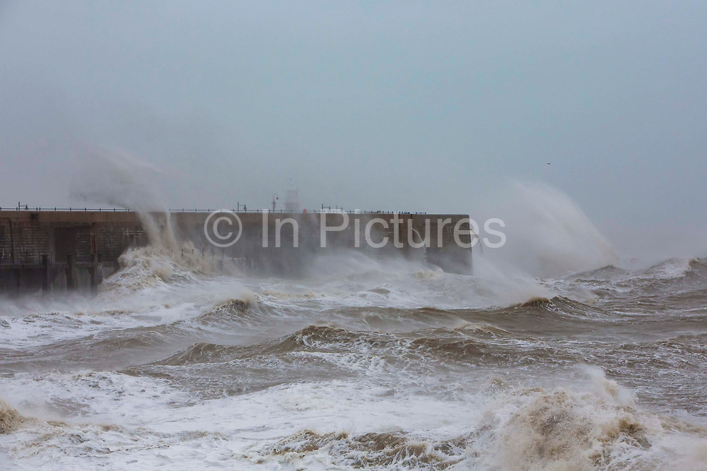 Waves cresting over Folkstone Harbour Arm as Storm Ciara swept in on February 9th 2020 in Folkestone, United Kingdom. Amber weather warnings were put into place by the MET office as gusts of up to 90mph and heavy rain swept across the UK. An amber warning from the MET office expects a powerful storm that will disrupt air, rail and sea links travel, cancel sports events, cut electrical power and damage property.