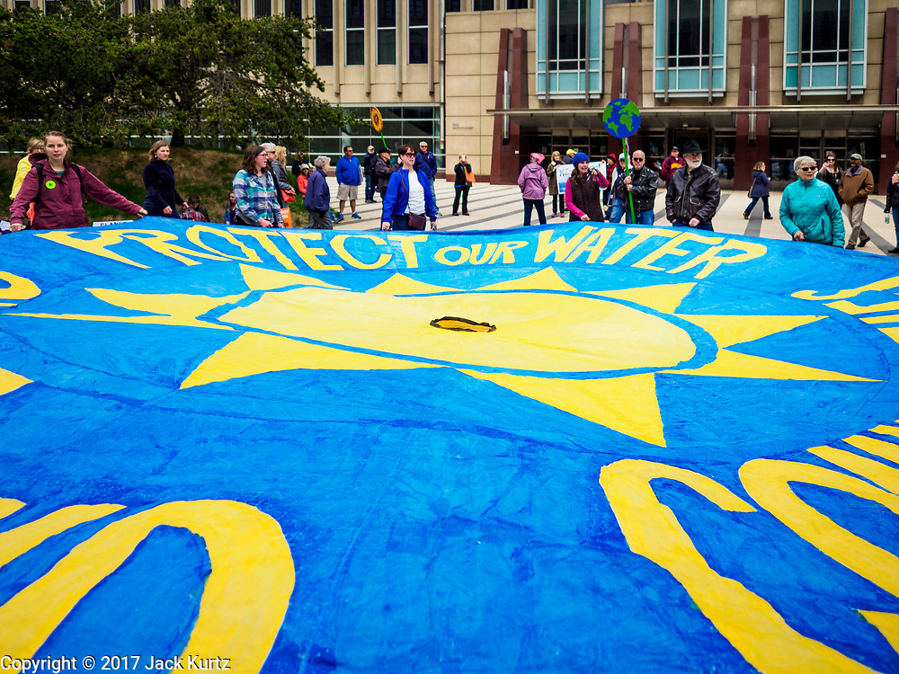 """29 APRIL 2017 - MINNEAPOLIS, MINNESOTA: People open a """"Protect our Water"""" banner in front of the federal courthouse in Minneapolis before the People's Climate Solidarity March. Thousands of people marched through downtown Minneapolis and rallied around the US Federal Courthouse to participate in the People's Climate Solidarity March. The Minneapolis march coincided with other marches to protest the climate change policies of President Trump and the Republican Party that were held across the US. It took place just one week after a series of large marches in support science and fact based decision making.     PHOTO BY JACK KURTZ"""