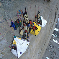 Hanging Portaledge camp & haul bags high on Great Sail Peak, Baffin Island, Canada.