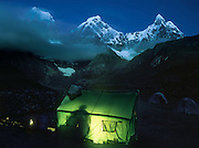 """A cooking tent glows green at dawn on a trek in the Cordillera Huayhuash, Andes Mountains, Peru, South America. Yerupaja Grande (left, east face, 6635 m or 21,770 ft) is the second-highest peak in Peru, highest in Cordillera Huayhuash, and highest point in the Amazon River watershed. At center is Yerupaja Chico (20,080 feet). On right is Mount Jirishanca (""""Icy Beak of the Hummingbird,"""" 6126 m or 20,098 feet). Published in Wilderness Travel Catalog of Adventures 2013. Published in """"Light Travel: Photography on the Go"""" book by Tom Dempsey 2009, 2010."""
