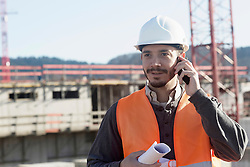 Young male engineer holding blueprint and talking on a mobile phone at construction site, Freiburg Im Breisgau, Baden-Wuerttemberg, Germany