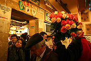 """A asian flower seller at """"Tasca do Chico"""". This is one of the typical spots were to see live perfomances of Fado music and were the audience can spontaneously participate and also ask to sing. It is located in  Bairro Alto neighborhood"""