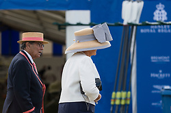 © Licensed to London News Pictures. 04/07/2018. Henley-on-Thames, UK. A woman wearing a large hat walks past rowing oars at day one of the Henley Royal Regatta, set on the River Thames by the town of Henley-on-Thames in England. Established in 1839, the five day international rowing event, raced over a course of 2,112 meters (1 mile 550 yards), is considered an important part of the English social season. Photo credit: Ben Cawthra/LNP