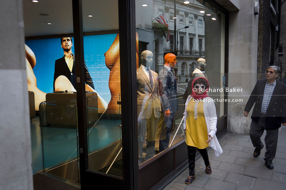 An eccentric looking woman passes-by Suitsupply, a fashion shop on Vigo Street in London's West End. Wearing large, owl-like glasses and a bright red scarf, the woman walks past a line-up of three mannequins dressed in stylish suits for the London gentleman. In their shop window, we can see a reflection of the Union Jack flag of other couture fashion houses in Saville Row, where Vigo Street forms a junction near Regent Street.