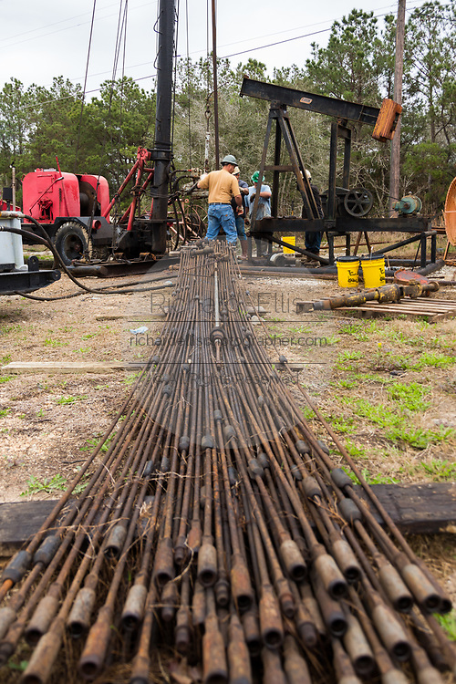 Oil workers sink pipe using a derrick to drill for crude in Evangeline, Louisiana. The oil fields were the first wells in Louisiana.