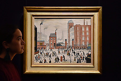 """© Licensed to London News Pictures. 17/11/2017. London, UK.  London, UK.  17 November 2017. A staff member views """"The Rush Hour"""", 1964, by L.S. Lowry (Est. GBP 0.8-1.2m).  Preview upcoming auctions of Modern & Post War British Art and Scottish Art taking place at Sotheby's, New Bond Street, on 21 and 22 November. Photo credit: Stephen Chung/LNP"""
