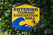 "A bold sign ""ENTERING TSUNAMI EVACUATION AREA"" shows a person running towards threatening waves. Laupahoehoe Point County Park, on the Hamakua Coast, Big Island, Hawaii, USA."
