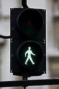 Green walk symbol on pedestrian crossing lights, London, United Kingdom